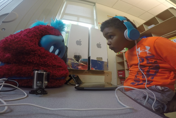 child peers at furry robot across a table